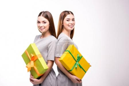portrait of smiling twins with wrapped gifts in hands looking at camera