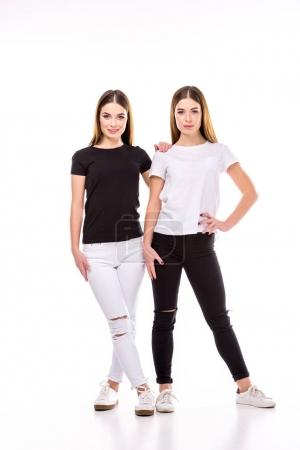 twins in black and white stylish clothing posing isolated on white