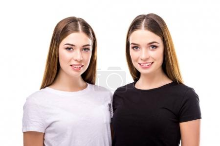 portrait of smiling twins in black and white stylish clothing isolated on white