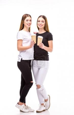cheerful twins with coffee to go in hands looking at camera isolated on white