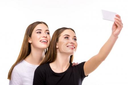 portrait of smiling twins taking selfie on smartphone together isolated on white