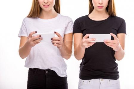 cropped shot of women holding smartphones in hands isolated on white