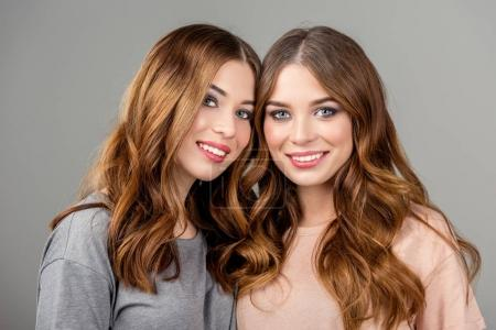 portrait of beautiful smiling twin sisters looking at camera isolated on grey
