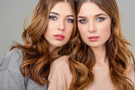 portrait of beautiful twin sisters looking at camera isolated on grey