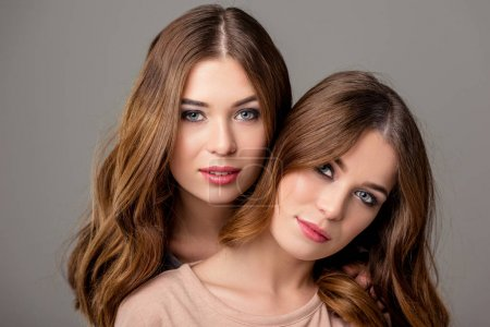portrait of beautiful twin sisters with bright makeup looking at camera isolated on grey