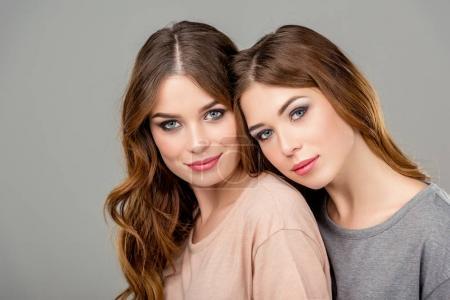 Photo pour Portrait de deux soeurs jumelles attrayant en regardant caméra isolée sur fond gris - image libre de droit