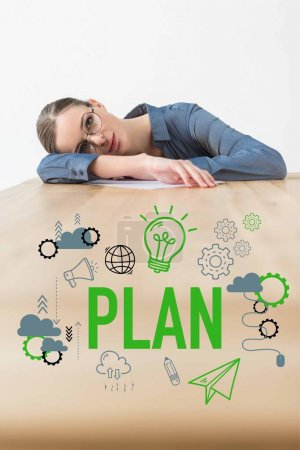 Tired businesswoman lying on table in office with plan inscription and business icons