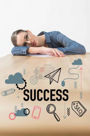 Tired businesswoman lying on table in office with success inscription and business icons