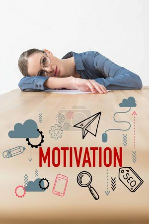 Tired businesswoman lying on table in office with motivation inscription and business icons