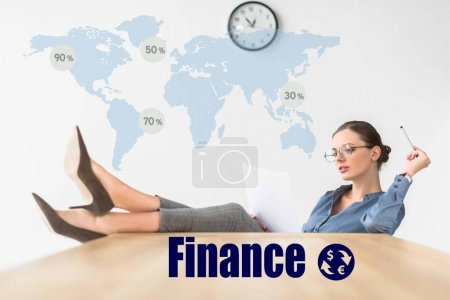 Photo for Businesswoman reading documents and sitting with legs on table with finance inscription and world map - Royalty Free Image