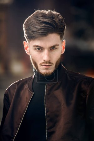 Brutal brunette bearded man with perfect hairstyle posing outdoors