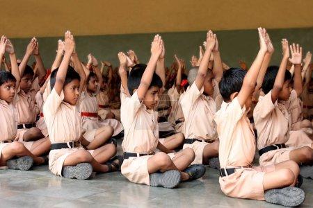 Photo pour Les écoliers qui font du yoga avec les professeurs - image libre de droit