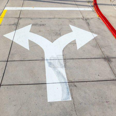 Photo pour Flèches et lignes sur l'asphalte pour indiquer la direction de la conduite - image libre de droit