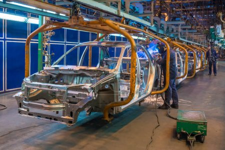 Assembly line of car production. Manual welding. B...