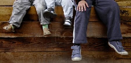 Photo pour Les pieds des garçons sur fond de bois - image libre de droit