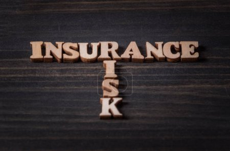 INSURANCE and RISK words on wooden background.