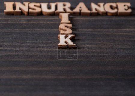 Photo pour Assurance et mots risque sur fond en bois - image libre de droit