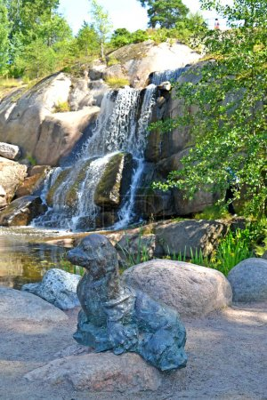 KOTKA, FINLAND - JULY 12, 2014: A sculpture of a seal against the background of the Putouskalli falls. Water Sapokka park