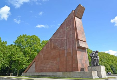 BERLIN, GERMANY - AUGUST 13, 2017: A sculpture of the grieving soldier about the lowered a little granite flag. Treptov-park