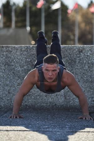 Male athlete doing Incline push ups outside