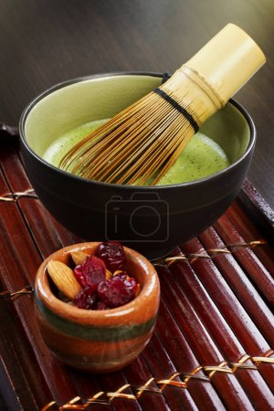 Matcha green tea with whisk in bowl