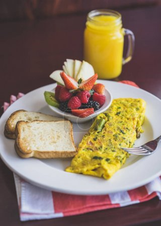 Gluten free breakfast omelet with toasts, berries bowl and orange juice