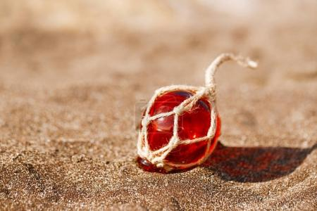 red Glass float on sand