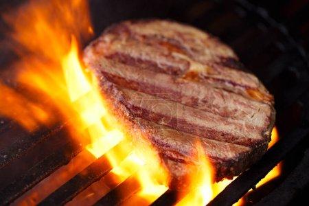 ribeye rib eye roast beef steak on bbq barbecue grill with flame. Shallow dof.