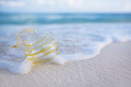 Photo pour Boule en verre clair Noël sur la plage avec fond marin - image libre de droit
