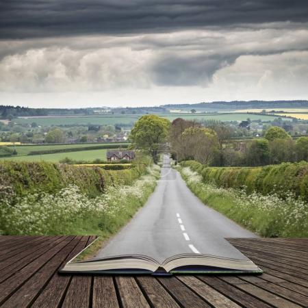 Photo for Landscape image of empty road in English countryside with stormy sky overhead concept coming out of pages in open book - Royalty Free Image
