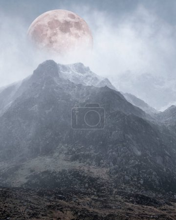 Beautiful digital composite image of Supermoon above mountain range giving very surreal fantasy look to the dramatic landscape image