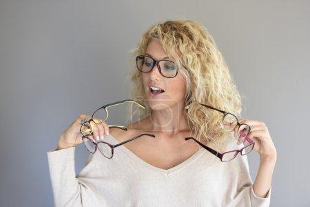 woman  choosing between different eyeglasses