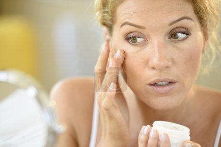 woman putting cosmetics on