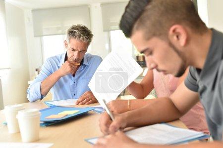 Photo pour Étudiants remplissant les formulaires d'inscription - image libre de droit