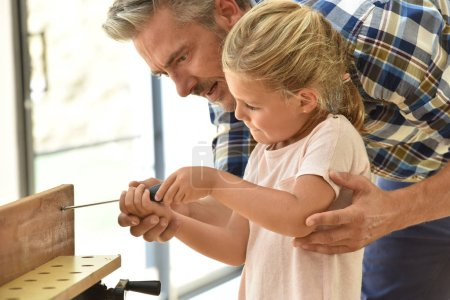 Photo for Daddy teaching daughter how to use screwdriver - Royalty Free Image