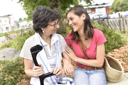 Senior woman with home carer sitting in park...