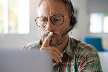 Photo for Portrait of man with eyeglasses connected with laptop - Royalty Free Image