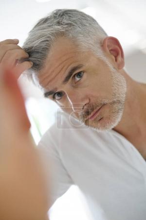 Photo pour Homme de 40 ans vérifiant les cheveux devant le miroir - image libre de droit
