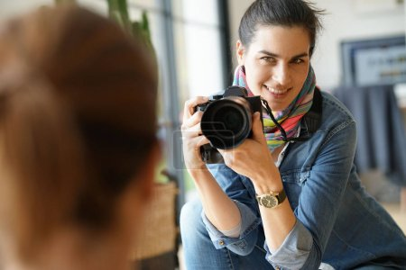Photographer in private house taking picture of model