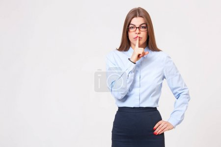 "Studio portrait of young beautiful business woman gesturing ""shh"