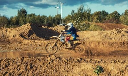 Photo for Arnoldsweiler, Germany, October 05,2017:Extreme Motocross MX Rider riding on dirt track on a sunny late summer day on public training session in preparation for Motocross event. - Royalty Free Image
