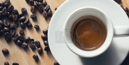 White Coffee Cup filled with Espresso on wooden table with coffee beans. table Top view.