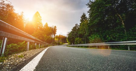 Photo for Highway into Silent Forest in spring with beautiful bright sun rays - wanderlust - Royalty Free Image