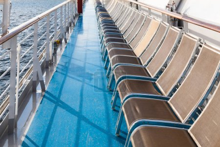 Row of sunbathing chairs on deck of liner