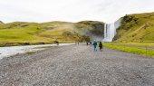 people walk to Skogafoss waterfall in Iceland