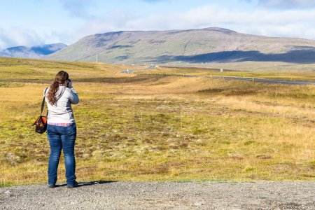 the tourist photographs a landscape in Iceland