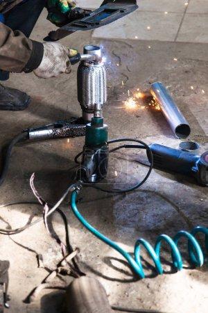 Photo pour Réparation du silencieux à ondulation du système d'échappement dans l'atelier automobile - soudeur fixe le tuyau sur silencieux à ondulation par soudage à l'argon - image libre de droit
