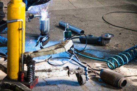 Photo pour Réparation du silencieux à ondulation du système d'échappement dans l'atelier automobile - le mécanicien soude le tuyau sur le silencieux à ondulation par soudage à l'argon - image libre de droit
