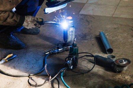 Photo pour Réparation du silencieux à ondulation du système d'échappement dans l'atelier automobile - soudeur soude le tuyau sur silencieux à ondulation par soudage à l'argon - image libre de droit