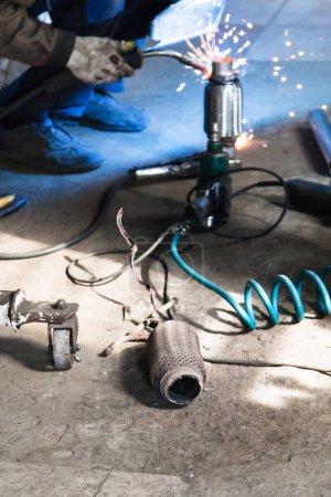 Photo pour Réparation du silencieux à ondulation du système d'échappement dans l'atelier automobile - vieux silencieux à ondulation brûlée sur le sol de l'atelier - image libre de droit